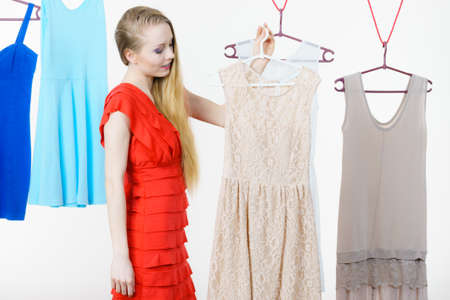 Young blonde long hair woman in clothes in shop or wardrobe choosing summer outfit, dresses hanging on clothing hangers, on white. Sale shopping fashion and style concept