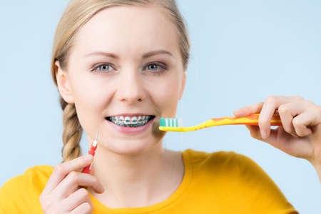 Dentist and orthodontist concept. Young woman smiling cleaning and brushing teeth with braces using toothbrush 版權商用圖片 - 93407381