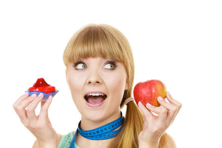 Woman with measuring tape holds in hand cake and apple fruit choosing, trying to resist temptation, make the right dietary choice. Weight loss diet dilemma gluttony concept. Isolated on white