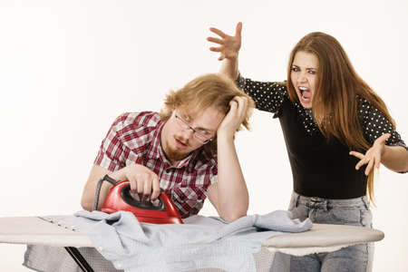 Woman trying to convince his man to do ironing, husband being bored and tired. Household domestic life problems.