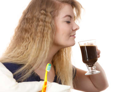 Funny woman holding black coffee and toothbrush being late. Getting morning energy, hurry up before going to work.