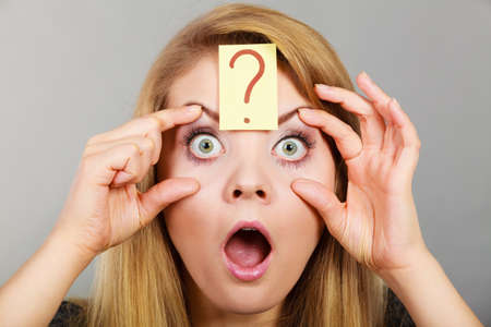 Woman having weirdly big wide open eyes with question mark forehead focusing on something or being in shock, funny face expression of female looking at things.