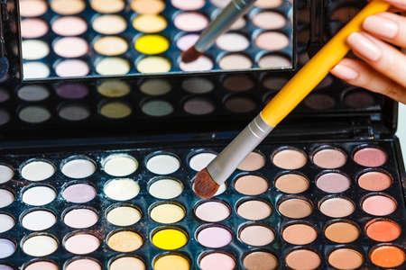 Cosmetische schoonheidsprocedures en make-overconcept. De vrouw houdt palet en borstel van make-up het professionele oogschaduwen. Make-up solliciteren.