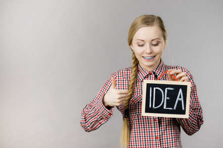 Happy positive young woman holding idea sign banner on black board. Studio shot on grey.