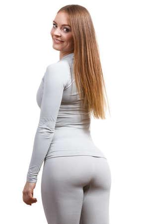 フィットフィットネススリムな女性、ホットグレーのスポーツサーモリネン下着、長袖トップとレギンスを着ているスポーティな女の子。白で隔離