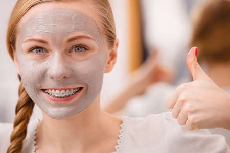 Skincare. Young positive woman with grey clay mud mask on her face. Female taking care of skin condition. Spa beauty treatment.