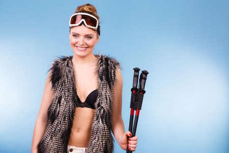 Winter sport activity concept. Atractive smiling girl wearing black bra, ski goggles and furry waistcoat holding ski poles, blue background studio shot.