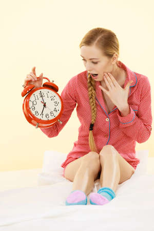Shocked young woman wearing cute pink pajamas holding big red old fashioned clock showing sleep time being late