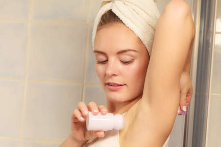 Woman applying stick deodorant in armpit. Girl putting antiperspirant in underarms in bathroom. Daily skin care and hygiene.