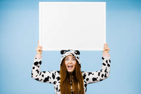People dressed up like animals concept. Happy crazy woman in funny cow pajamas costume holding blank board sign