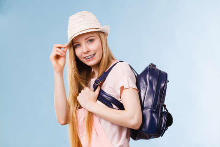 Happy young blonde teenage girl going to school or college wearing backpack. Archivio Fotografico