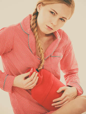 Painful periods and menstrual cramp problems concept. Woman having stomach cramps lying on bed holding hot water bottle feeling very unwell.