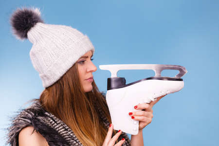 Winter sport activity concept. Girl wearing warm hat and furry waistcoat holding and looking at ice skate, blue background studio shot. Stock Photo
