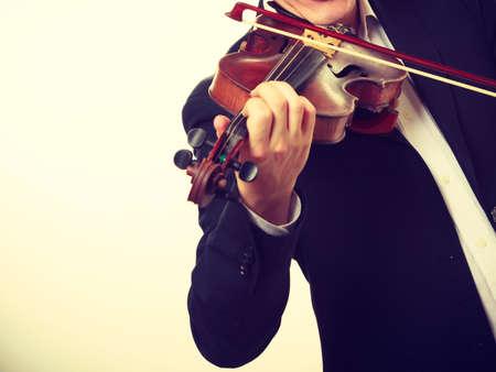 音楽への情熱、趣味のコンセプト。木製のバイオリンでエレガントに演奏する若い男をクローズアップ。白い背景にスタジオショット 写真素材 - 94704608