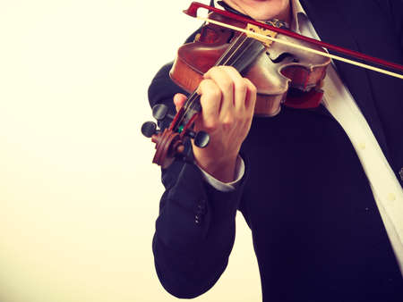 Music passion, hobby concept. Close up young man man dressed elegantly playing on wooden violin. Studio shot on white background Stock Photo