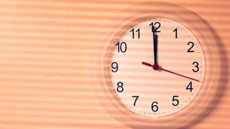 Clock hanging on wall ticking showing twelve hours Stock Photo
