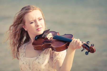 Music love, hobby and everyday passion concept. Woman on beach near sea playing on violin Stock Photo