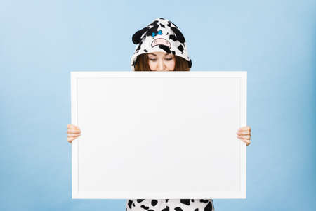 Teenage girl in funny nightclothes, pajamas cartoon style covering her face with blank empty banner board., looking down. Advertisement copyspace.
