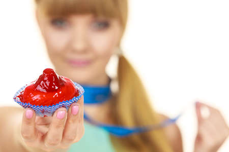 Woman with blue measuring tape around her neck holds in hand cake cupcake. Weight loss diet dilemma concept. Isolated on white