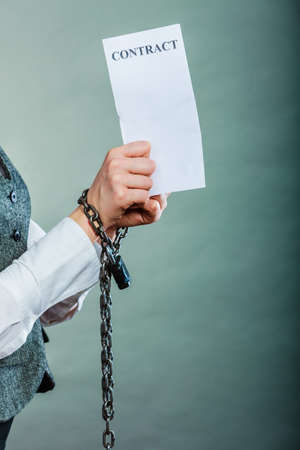 Business concept. Serious woman businesswoman with chained hands holding contract, side view grungy background