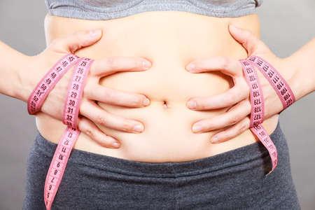 Van buikvet, dieet, gewichtsverlies of gewichtstoename afkomen. Vrouw wat betreft maagholding die band meet Stockfoto