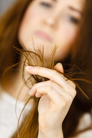 Worried woman looking at her dry split long brown hair ends, thinking of good treatment. Haircare and hairstyling concept.