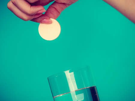 Vitamins, health, medicines. Person throwing vitamin mineral supplement effervescent tablet into glass of water. Studio shot on blue background