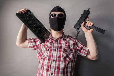 Crazy hacker man. Unrecognizable guy wearing black balaclava holding gun and keyboard. Hate speech on the internet. Stock Photo
