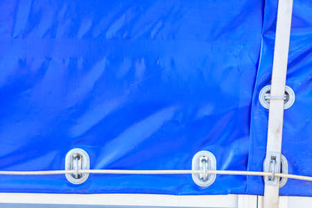 Detailed close up of blue tarpaulin with wires and ropes. Truck details concept.