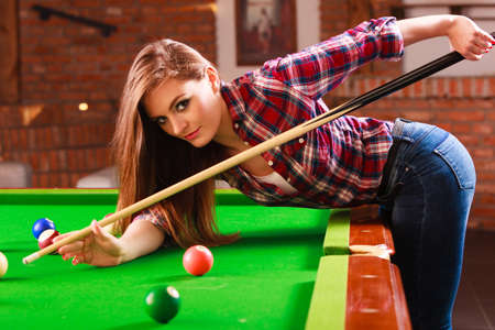 Competition concept. Young focused girl having fun with billiard. Pretty fashionable woman spending time on playing rivalry. 스톡 콘텐츠