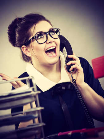 Happy, positive shocked business woman smiling sitting working at desk full off documents in binders calling someone.