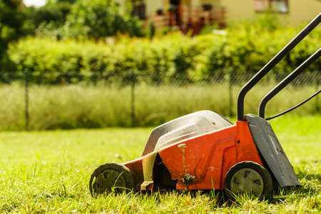 Gardening, garden service. Old lawn mower cutting green grass in backyard. Mowing field with lawnmower in sunny day. Stok Fotoğraf - 95897894
