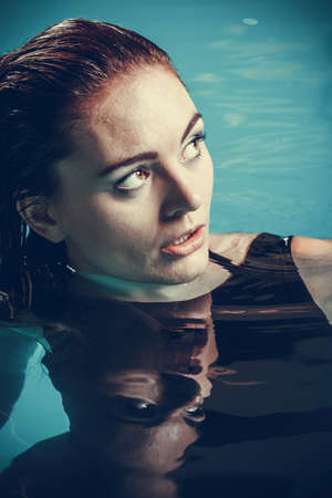 Portrait of sexy seductive woman wearing black dress in swimming pool water. Young attractive alluring girl floating. 스톡 콘텐츠