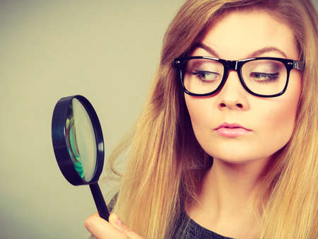 Blonde woman holding magnifying glass investigating something and looking closely, trying to find solution.