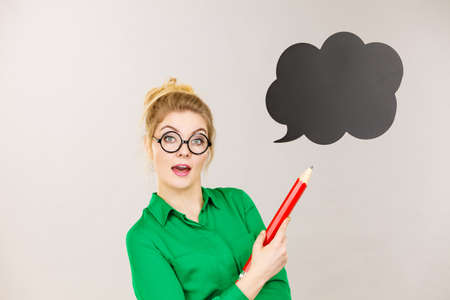 Student looking woman wearing nerdy eyeglasses holding big oversized pencil thinking about something, black speech bubble next to her Stock Photo