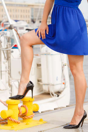 Dominant feminist woman wearing high heels and short blue dress, standing one leg on big industrial bolt in marina.