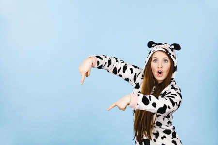 Happy teenage girl in funny nightclothes, pajamas cartoon style pointing down with positive surprised face expression, studio shot on blue. Advertisement concept Reklamní fotografie