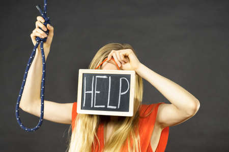 Suicidal unrecognizable skinny woman having face help sign on dark board next to hanging rope with knot. Standard-Bild