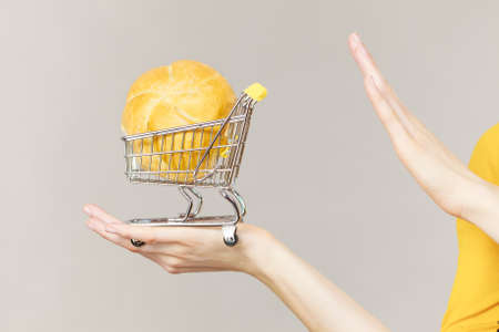 Buying gluten food products concept. Skeptical woman holding shopping cart trolley with bun breal roll showing stop gesture sign. Stock Photo