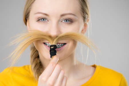 Woman making moustache out of braided blonde hair. Haircare, hairstyling having fun.