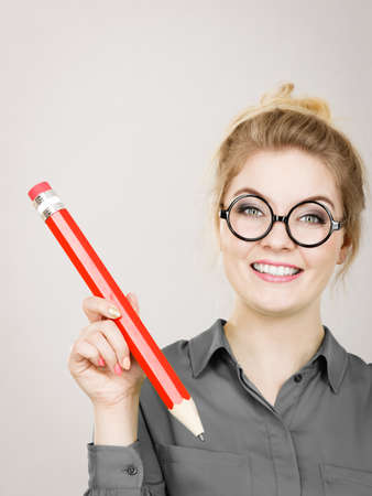 Positive joyful woman blonde student girl or female teacher wearing glasses holding big red pencil. Studio shot on grey