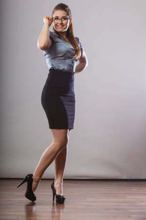 Teacher looking elegant woman wearing dark tight skirt, high heels, shirt and eyeglasses.