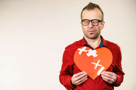 Bad relationships, breaking up, sadness emotions concept. Sad serious thinking adult man holding broken heart, on grey