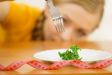 Sad young blonde woman dealing with anorexia nervosa or builimia having small green vegetable on plate. Dieting problems, eating disorder. Stock Photo
