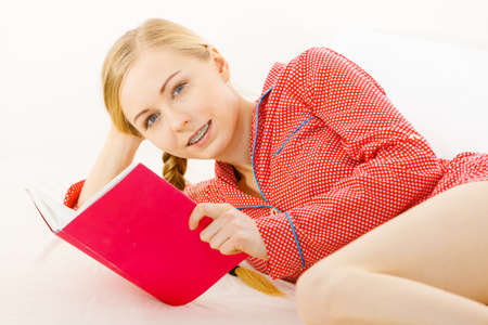 Girl lying in bed reading book. Young blonde female wearing red dotted pajamas relaxing at home on mattress. Stock fotó