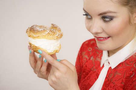 Concept de nourriture sucrée et de bonheur. Drôle joyeuse femme blonde tenant un délicieux gâteau choux puff avec de la crème fouettée, une expression de visage excitée. Sur gris Banque d'images