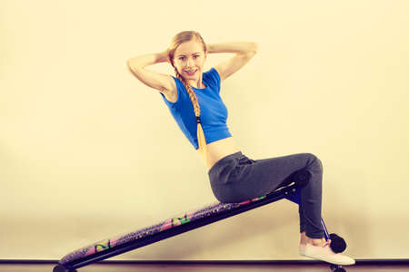 Young teenage woman training on bench for sit ups at home. Being fit and healthy, stomach muscles workout.