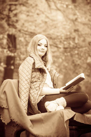 Autumn time education concept. Blonde girl with book. Attractive woman sitting on blanket in the park relaxing, foggy misty day Stock Photo
