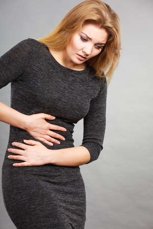 Woman having strong stomach ache. Syndroms of indigestion pregnancy. Female suffer on belly pain, holds hands on abdomen on grey