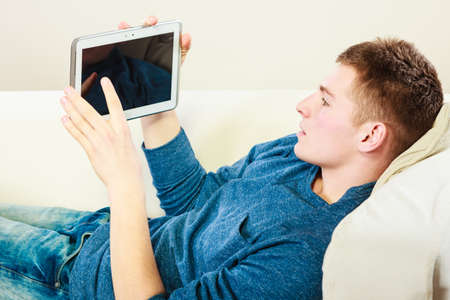 Modern technology home and relaxation concept. Young man with pc computer digital tablet on couch